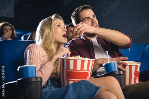 Leinwandbild Motiv emotional couple with popcorn watching film together in cinema