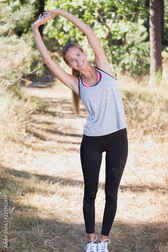 szczęśliwa młoda kobieta fitness rozciągania na zewnątrz na zachód słońca