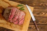 Steak sitting on cutting board next to knife - 220963643