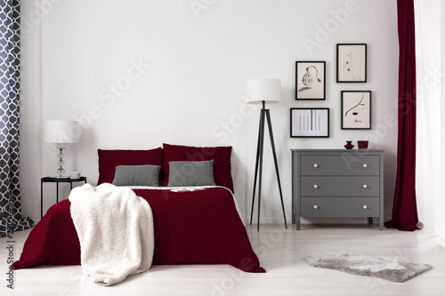 Real photo of a glamour bedroom interior with dark red bed, blanket, lamp and grey commode. Empty wall, place your painting - 220969050