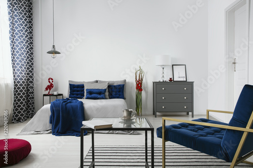 Real photo of a modern bedroom interior with a bed, commode, flower, coffee table, armchair and blue accents. Empty wall, place your painting - 220969086