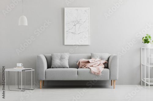 Leinwanddruck Bild Poster above grey sofa with pink blanket in living room interior with white lamp and plant. Real photo