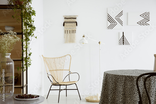 Leinwandbild Motiv Flowers on table near modern armchair in bright apartment interior with lamp and posters. Real photo
