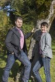 Young couple in trachten outfit outdoors on the sunny autumn day, with a trees background, Bavaria, Germany - 220970216