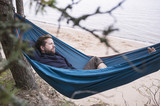 A bearded man lies relaxed in a hammock and squinting peering into the distance, against the background of a sandy beach and the sea.  - 220973848