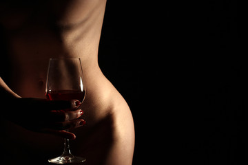 Nude woman with glass of red wine in her hand. Dark Background.