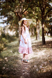 a girl walks along a forest path, dressed in a long dress and wide hat, bright sun and shadows, a beautiful summer day - 220976865