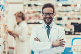 Portrait Smiling Pharmacist Working in Drugstore - 220978095
