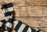 Striped wool scarf on brown wood background. Copy space - 220986628