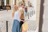 couple of shoppers with papers bags walking near shopwindows at city street - 220986894