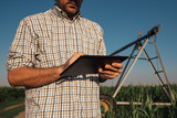 Farmer using tablet computer in cornfield with irrigation system - 220989033