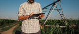 Farmer using tablet computer in cornfield with irrigation system - 220989099