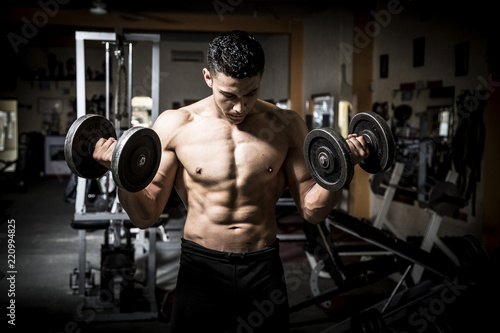 Young man exercising in dark and old gym - 220994825