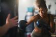 african american woman striking punching bag in home gym