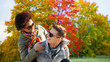 leisure, people and season concept - happy mixed race teenage couple having fun over autumn park background
