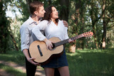 young couple walking in the forest, playing guitar and dancing, summer nature, bright sunlight, shadows and green leaves, romantic feelings - 221008852