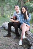 young couple sitting on a log in the forest and playing guitar, summer nature, romantic feelings - 221008877