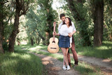 young couple walking in the forest, playing guitar and dancing, summer nature, bright sunlight, shadows and green leaves, romantic feelings - 221008896