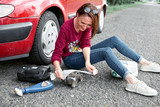a young girl sits near a broken car and makes repairs to the electric generator, next to her there are bad parts, tools and first aid kit - 221009043