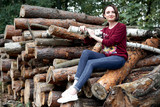 young girl having fun in the forest, posing near the logs - 221009097