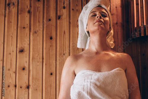 Woman sitting in a wooden spa with eyes closed. - 221033651