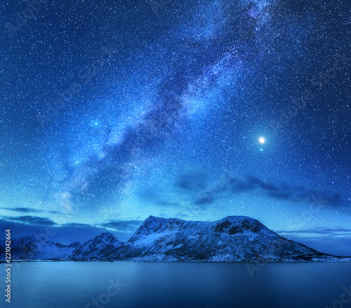 Bright Milky Way over snow covered mountains and sea at night in winter in Norway. Landscape with snowy rocks, starry sky, reflection in water, fjord. Lofoten Islands. Space. Beautiful milky way