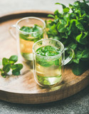 Hot herbal mint tea drink in glass mugs over wooden tray with fresh garden mint leaves, selective focus, close-up - 221051218