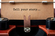 Motivational poster, inspiration to create and storytelling concept with close up on a old typewriter and the text - tell your story - on vintage brown paper