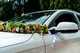 White Wedding car with Wedding decorations flowers