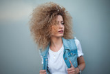 Young attractive woman with very lush hair. Portrait of a beautiful girl in denim vest - 221076266