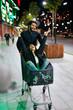 Leinwanddruck Bild - Couple Having Fun In Shopping Mall Cart Outdoors In Evening