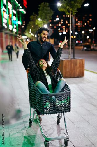 Leinwanddruck Bild Couple Having Fun In Shopping Mall Cart Outdoors In Evening