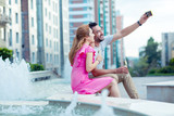 Our photo. Nice cheerful man taking a selfie while sitting together with his girlfriend - 221078039
