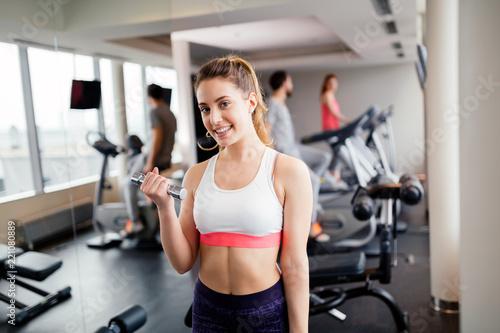 Leinwandbild Motiv Beautiful woman lifting weights in gym