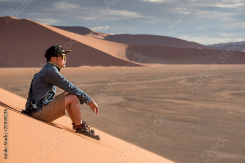 Young Asian man traveler and photographer looking at scenery while sitting on sand dune in Namib desert of Namibia, Africa. Travel photography concept - 221081226
