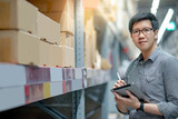 Young Asian man worker doing stocktaking of product in cardboard box on shelves in warehouse by using digital tablet and pen. Physical inventory count concept