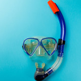 Diving equipment. Snorkeling mask and tube on blue background. Colorful background. Top view. Copy space. Flat lay - 221083405