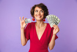 Photo of excited young woman 20s wearing big straw hat smiling while holding credit card and fan of dollar cash, isolated over white background