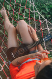 Close up view of Woman with ukulele in hammock in the garden - 221092608