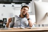 Happy business man talking by smartphone and drinking coffee - 221094081
