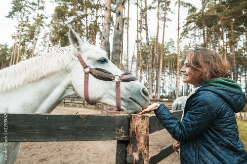 Fototapeta Beautiful young woman stroking the nose of a gray horse, love and care for animals
