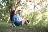 young couple sitting on the grass in the forest and looking on sunset, summer nature, bright sunlight, shadows and green leaves, romantic feelings - 221098815