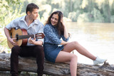 young couple sitting on a log by the river and playing guitar, summer nature, bright sunlight, shadows and green leaves, romantic feelings - 221098852