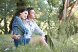 young couple sitting on the grass in the forest and looking on sunset, summer nature, bright sunlight, shadows and green leaves, romantic feelings - 221098877