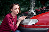 a young girl stands at a broken car and holds a bad spare part, an electric generator, does not understand how to repair - 221099064