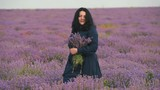 A girl in a dress is walking along the lavender field with a bouquet of lavender. - 221101414