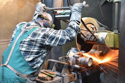 Leinwanddruck Bild Industriearbeiter im Metallbau bearbeitet Werkstück mit Trennschleifer // Industrial worker in metal construction processes workpiece with cut-off grinder