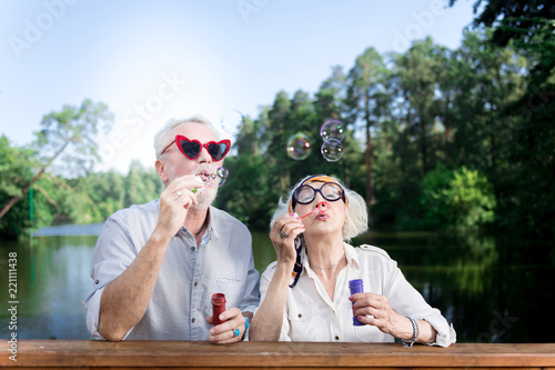 Red sunglasses. Funny elderly man wearing red heart shape sunglasses using soap bubbles standing near his wife