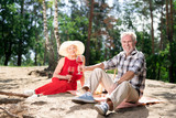 Picnic on sand. Couple of beaming elderly wife and husband sitting on sand having very romantic picnic near river - 221113429