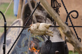 A medieval roasting spit with cauldron or cooking pot suspended on a hanger over an open fire - 221132097